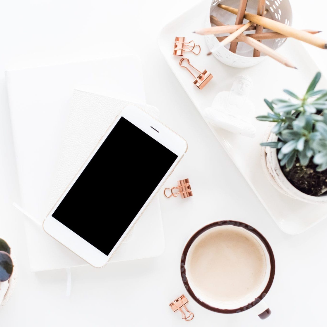 White home office desk flat lay with coffe, smartphone and succulents, clean stylish bloggers workspace, phone screen mock-up